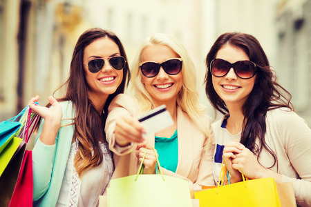 gift spending: shopping and tourism concept - beautiful girls with shopping bags and credit card in ctiy
