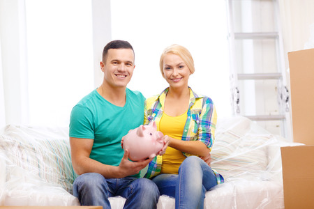 moving, home and couple concept - smiling couple with piggybank in new home photo
