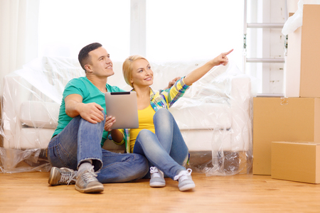 new direction: moving, home, technology and couple concept - smiling couple sitting on the floor with tablet pc computer in new home Stock Photo