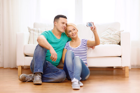 love, family, technology and happiness concept - smiling couple taking self portrait picture with digital camera at home photo