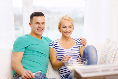 unhealthy living: food, love, family and happiness concept - smiling couple with popcorn watching movie at home