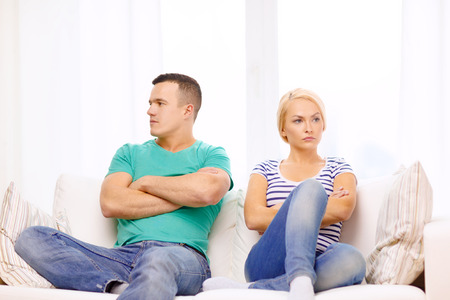 love, family and happiness concept - unhappy couple not speaking after having argument at home photo