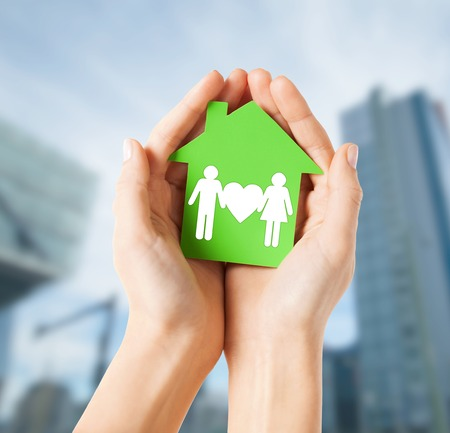 real estate and family home concept - closeup picture of female hands holding green paper house with family photo
