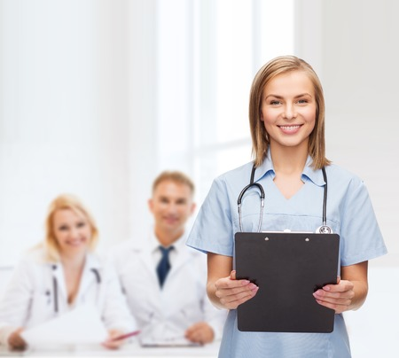 healthcare and medicine concept - smiling female doctor or nurse with clipboard and stethoscope photo