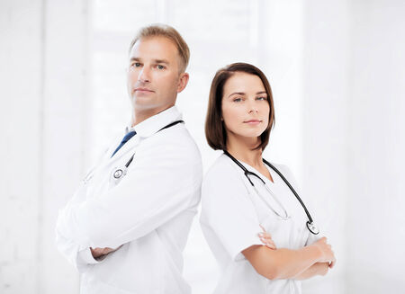 physiotherapists: healthcare and medical concept - two doctors with stethoscopes
