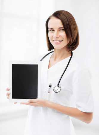 healthcare and medical concept - female doctor with tablet pc photo