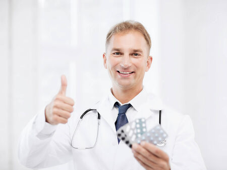 healthcare, medical and pharmacy concept - male doctor with packs of pills