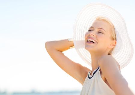 sombrero: la moda, la felicidad y el estilo de vida concepto - mujer hermosa en el sombrero que goza de verano al aire libre