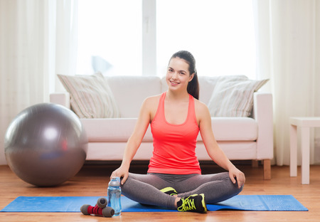 fitness equipment: fitness, home and diet concept - smiling teenage girl sitting on mat with sports equipment at home
