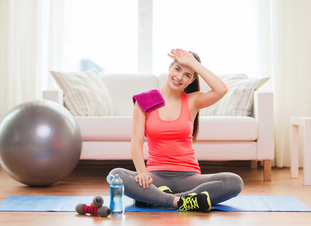 woman in towel: fitness, home and diet concept - smiling teenage girl with bottle of water after exercising at home