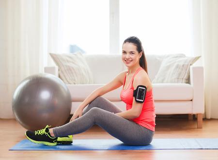 armband: Fitness, sportm casa e dieta concetto - sorridente ragazza adolescente con execising bracciale a casa