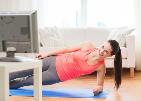 mujeres fitness: aptitud, el hogar y el concepto de dieta - sonriendo adolescente haciendo tabla lateral y viendo la televisi�n en casa