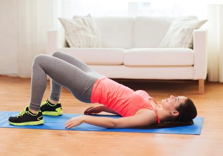 haciendo ejercicio: aptitud, el hogar y el concepto de dieta - sonriendo mujer haciendo ejercicios para las piernas y las nalgas en el suelo en casa