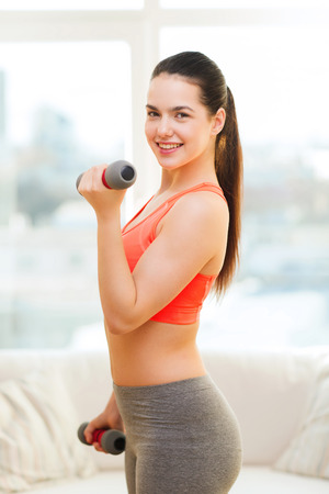 fitness, home and diet concept - smiling redhead girl exercising with heavy dumbbells at home photo