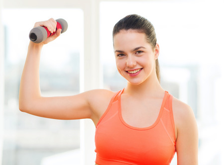 fitness, home and diet concept - smiling redhead girl exercising with heavy dumbbell at home photo