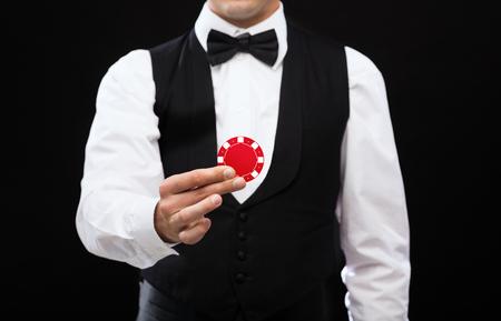 マジック、パフォーマンス、サーカス、カジノ、ショーのコンセプト - 赤いポーカーの映画チップを保持しているカジノ ディーラー 写真素材