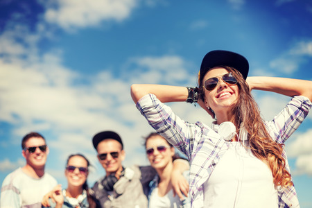 group of teenagers: summer holidays and teenage concept - teenage girl in sunglasses, cap and headphones hanging out with friends outside