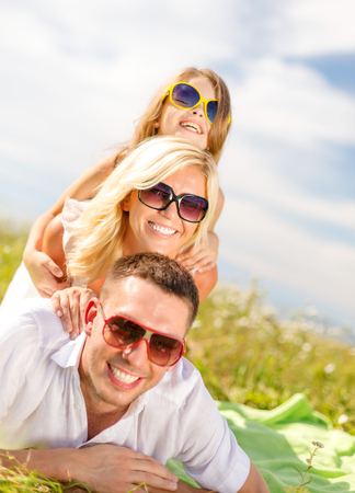 summer holidays, family, child and happy people concept - smiling family in sunglasses lying on blanket outdoors photo