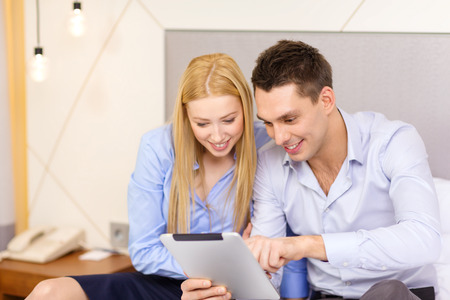 trave: business, hotel, trave and technology concept - smiling couple with tablet pc computer in hotel room