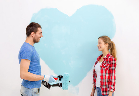 repair, building and home concept - smiling couple painting big heart on wall at home photo