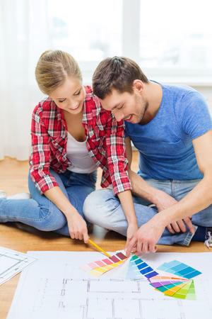 repair, interior design, building, renovation and home concept - smiling couple looking at color samples at home photo