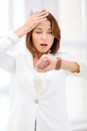 business and time management concept - stressed businesswoman looking at wrist watch in office Zdjęcie Seryjne