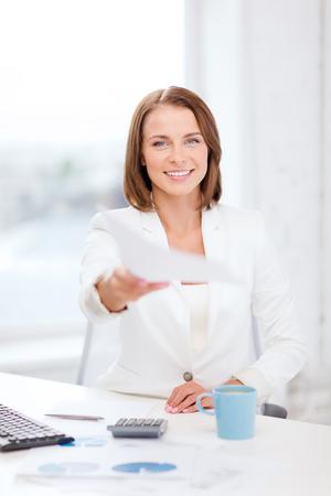 adn: empresaria sonriente dando papeles en la oficina - de negocios adn concepto de educación Foto de archivo