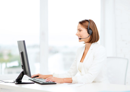 call center agent: business, communication, technology and call center concept - friendly female helpline operator with headphones and computer call center
