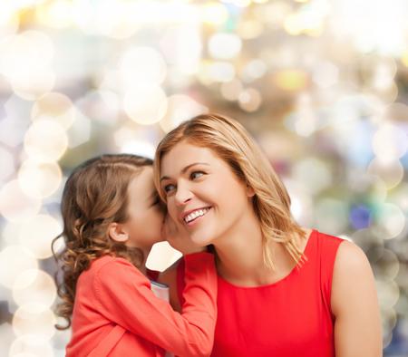 niños platicando: familia, niño y concepto de la felicidad - sonriente madre e hija susurrando chismes