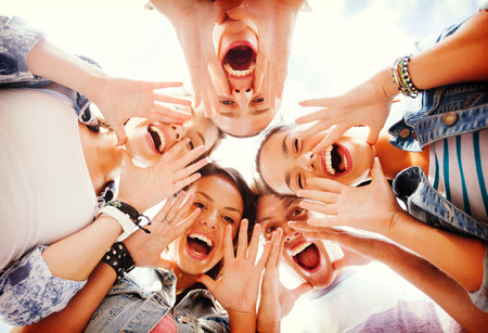 chilling out: summer holidays and teenage concept - group of teenagers looking down and screaming Stock Photo