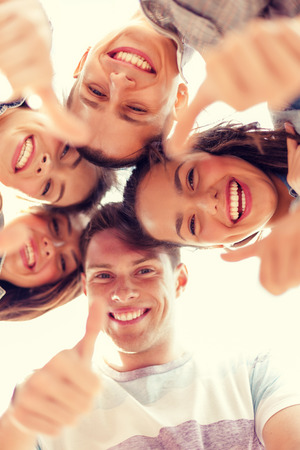 looking down: summer holidays and teenage concept - group of smiling teenagers looking down and showing thumbs up