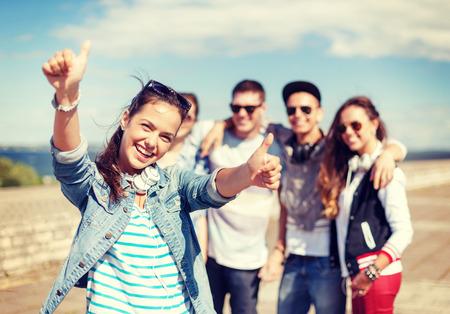 juventud: vacaciones de verano y concepto de adolescente - adolescente en gafas de sol y los auriculares que cuelgan hacia fuera con amigos fuera y mostrando los pulgares para arriba