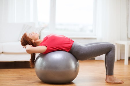 fitness, home and diet concept - smiling redhead girl exercising with fitness ball at home photo