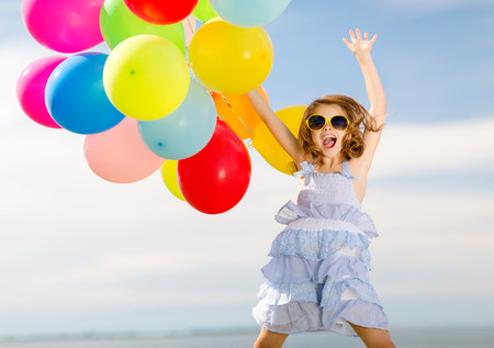 vacaciones de verano, celebración, niños y concepto - niña feliz saltando con globos de colores al aire libre