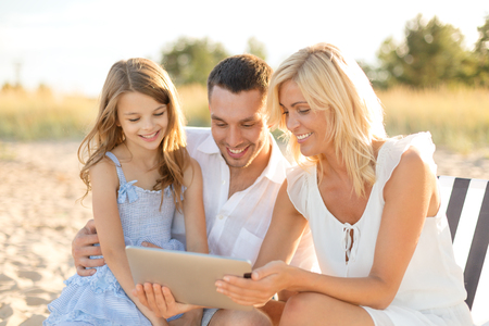 summer holidays, family, child and technology concept - smiling family at beach with tablet pc computer photo