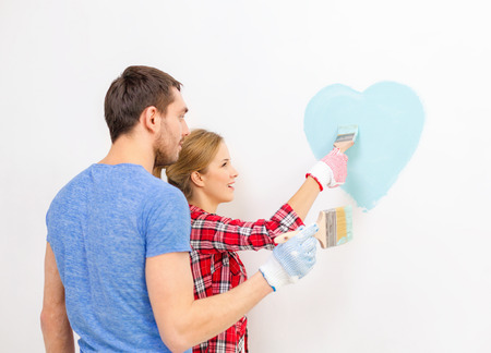 repair, building and home concept - smiling couple painting small heart on wall at home photo