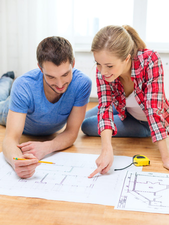 repair, building, renovation and home concept - smiling couple looking at blueprint at home