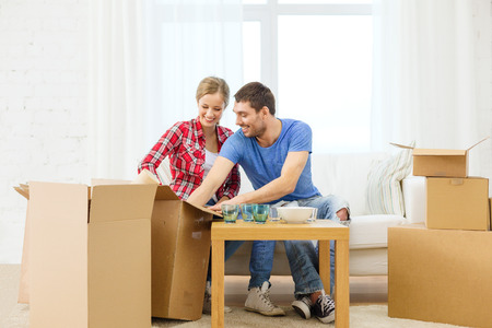 repair, building and home concept - smiling couple unpacking kitchenware photo