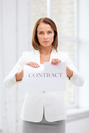 breaking the rules: business and office, legal concept - concentrated businesswoman tearing contract in office