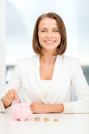 business and money saving concept - smiling businesswoman putting euro coins into piggy bank photo