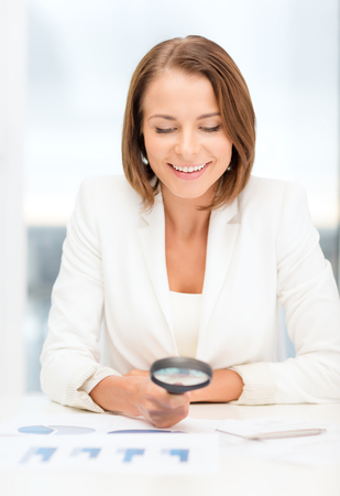 business, education, school, documents, people concept - smiling businesswoman or student working with graphs in office photo