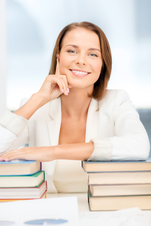 education and business concept - dreaming young businesswoman with many books indoors photo