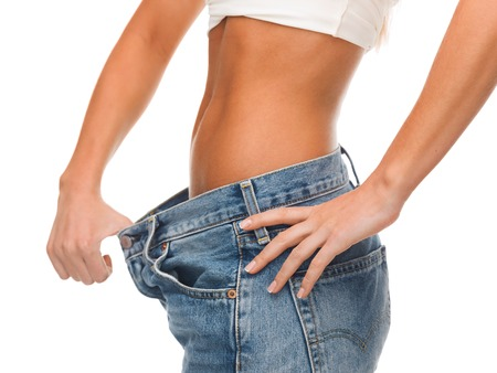 weight loss success: healthcare, diet and fitness concept - close up of female showing big jeans
