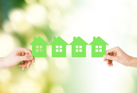 dreams of city: real estate and family home concept - closeup picture of male and female hands holding many green paper houses Stock Photo
