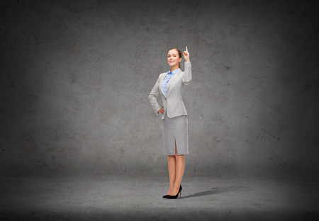 business and education concept - attractive young businesswoman with her finger up photo
