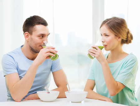 food, home, couple and happiness concept - smiling couple having breakfast at home Stock Photo