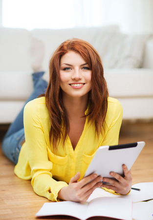 business, education and technology concept - smiling female student with notebooks and tablet pc computer at home photo