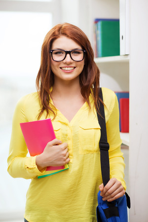 beautiful redhead: education concept - smiling redhead female student in eyeglasses with laptop bag and notebooks in library