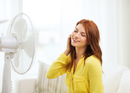 cooling: summer, weather and equipemt concept - smiling redhead teenage girl with big fan at home