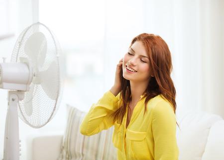 fresh air: verano, tiempo y concepto equipemt - sonriente adolescente pelirroja con ventilador grande en casa